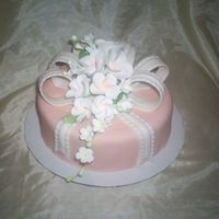 A Gift For Mom mmf fondant in a peach color with a white mmf loop bow and ribbon and gumpaste flowers
