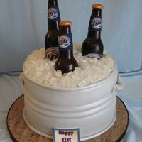 Beer Tub With Sugar Bottles Cake is covered in fondant and then spryed w/luster dust. Ice is rock candy and bottles are made out of sugar. lables are edible images....