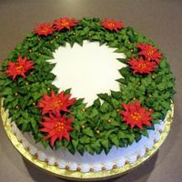 Christmas Wreath '06 Chocolate cake w/cherry filling, vanilla buttercream frosting. Poinsettias are RI and dusted with gold pearl (hard to tell in photo). Gold...