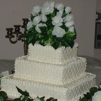 Pb271056.jpg My first wedding cake two years ago. I didn't know how to do floralarrangements, so I purchased a flower for the top. I used edible...