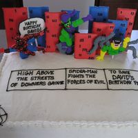 Comic Book Cake Buildings are made with color flow icing. Spider Man characters are made with royal icing, piped onto waxed paper.