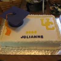 Graduation Cake 11x15 white cake with white buttercream icing. The graduation cap and UC emblem and letters are fondant. The tassle is made from cross-...