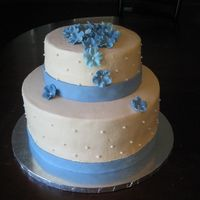 Simple Blue Wedding Cake covered in buttercream with fondant ribbon and fondant molded flowers with pearl accents.