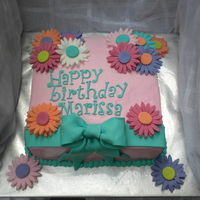 "Gerbera Birthday Cake A 10"" square vanilla cake covered in white choc buttercream and decorated in brightly colored fondant gerbera's and a bow. This..."