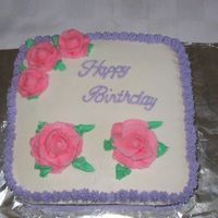 Birthday Cake Chocolate cake with strawberry buttercream filling and buttercream icing and decorations.