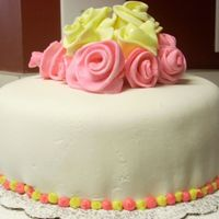 Pink/yellow Roses Pink and yellow roses out of fondant with white fondant. Strawberry cake. First time using fondant.