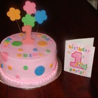 "Flowers And Dots Buttercream base with fondant accents. Candy melts ""1""."