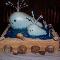 Mother And Baby Whale Buttercream icing on entire cake. White and milk chocolate shells. Crushed vanilla waffers to make the sand and piping gel for water. The...