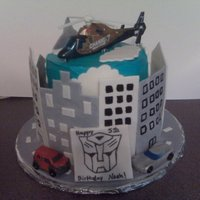 Transformers Birthday Cake! two tiered birthday cake with fondant/gumpaste buildings and road. Transformers birthday cake!
