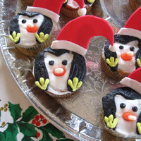 Christmas Penguins Cupcakes iced in buttercream with a fondant hat secured with a lollipop stick.
