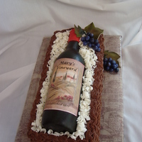 Wine Bottle Basket Gumpaste wine bottle on chocolate cake with choc buttercream for basket-- Fondant grapes and leaves.