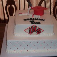 Graduation Cake bottom layer is redvelvet with cream chesse filling and top layer is chocoate. iced in Buttercream with all gumpaste accents. Square cakes...