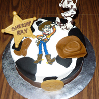 Woody, Toy Story Completely edible. 3 candle is made of chocolate, Woody is color flow piece. Cake is iced in buttercream with fondant cow spots, and the...