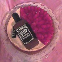 Cheese Cake With Jack Chocolate Bottle this is a plain cheese cake with a chocolate Jack bottle on top with a tiny store bought candy bottle next to it.