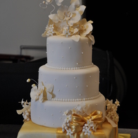 White And Gold Wedding Cake   Gumpaste flowers. Bottom tier covered in gold dust. Tiers flavors were yellow butter, chocolate, lady baltimore and carrot.
