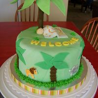 Jungle Baby Shower Orange cake covered in fondant. Fondant baby and animal cutouts. Plam tree made from gumpaste and fondant covered dowel.