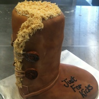 Ugg Boot All cake carved and covered in fondant. Fur is royal icing and we used chalk for the shading of the boot.