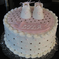 Lyla's Baby Shower   This is a buttercream frosting with fondant booties, blanket and dots on the sides.