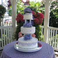 Laura's Cake The bride and groom actually designed this cake. The frosting is buttercream with purple buttercream details. The flowers are real. There&#...