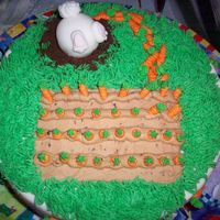 Bunny And Carrots This is a cake I did for my god mother for easter. The bunny ate too many carrots and can't get into his hole! HA!