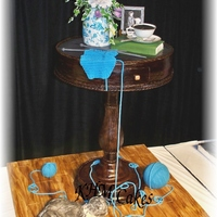 Life Size Mahagony Accent Table Cake.... The top of the table is hummingbird cake, the base is lemon pound cake. The center pedastol is pvc pipe wrapped in chocolate clay with the...
