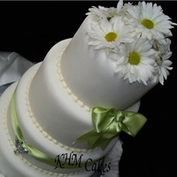 Butterfly Bling With Apple Green Ribbon on a 4 tier round stacked white cake covered in fondant with fresh daisies as the topper.