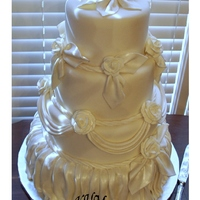 Ivory Fondant Covered Wedding Cake with draping and roses dusted with pearl luster dust.