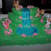 Fairy Cake Cake covered in butter cream and flowers fondant with toy fairies