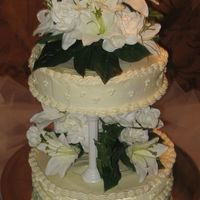 Wedding_Cake.jpg My first wedding cake. Classic white cake with a lemon icing. Silk flowers.