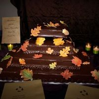 Autumn Wedding Cake 4 layers#1 bananas foster#2 pumpkin spice#3 chocolate#4 red velvetAll iced in chocolate ganache with gum paste accents.