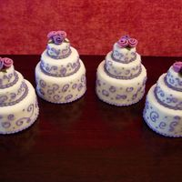 "Quartet Mini-Cakes 4"", 2"" and 1"" cakes stacked and covered in fondant with fondant flowers and royal icing designs."