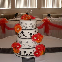Black And White Polka Dot/swirls Very fun to do black and white theme with hot pink and hot orange gerber daisies. All fondant except the swirls. Those were piped on with...