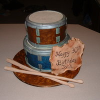 Two Tiered Drum Cake Set of two drums cake for a guys' birthday. Gumpaste drumsticks, and plaque. Cake is all fondant that was painted in different colors...