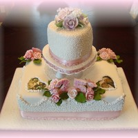 Roses And Cornelli Lace 2 tiered vanilla cake with raspberry creamy filling. Covered with vanilla buttercream icing and fondant; decorated with royal icing,...
