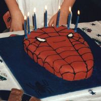 Spiderman Madeira cake cut into shape. Board covered with blue fondant and decorated with black fondant spider. Cake covered in red fondant and black...