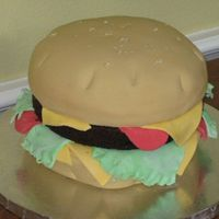 Burger Made for my son's 14th birthday. Yellow cake as burger and chocolate layer for burger. Covered in fondant with fondant cheese, lettuce...