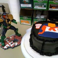 Judge Dredd Color flo picture with chocolate cake; covered in black fondant with black buttercream decoration. Inside is plain white buttercream.
