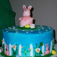 Easter Cake.  Chocolate cake with vanilla buttercream. Bunny and fence are fondant. Decorations are all buttercream with cadbury eggs and flower confetti...