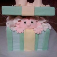 Baby In A Box! Made this for my neice's baby shower. The lid is foam, the baby face is fondant, the tissue paper is gumpaste and fondant, the cake is...