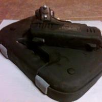 Handgun Gun and box are both cake, covered in Satin Ice. Bullets are gumpaste, painted with metallic americolor. Picture was taken after I wiped...