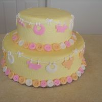 Quilted Babyshower Cake  Two layer white cake with white almond buttercream and orange preserve, covered in yellow tinted buttercream and decorated with fondant...