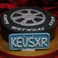 Tyre/wheel Cake - Kevin's Birthday Cake Cake for a man who loves his car. The plaque is a replica of his personalised licence plate. Cake is choc cake with dark choc ganache and...