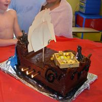 Pirate_Cake_Back.jpg this is my son's pirate cake. it is 3 sheet cakes carved and stacked with choclate icing, and a fondant railing. i'd never used...