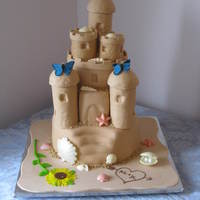 Sand Castle Cake This is my first wedding cake. The cakes are (from top to bottom) Red Velvet, French Vanilla and Dark Chocolate. They are covered in MMF...