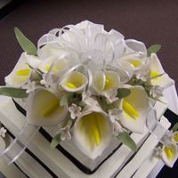 Calla Lillies These are gumpaste Calla Lillies and other small flowers. The leaves are gumpaste as well. The bow on top is ribbon.