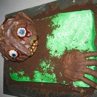 Groom's Cake This was a zombie that a friend and I made. The groom loves zombies. You could see the brain in the back of the head, but I'm not sure...