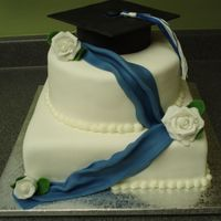 Graduation Cake (Blue & White)  Chocolate cake with Satin Ice fondant. The flowers and graduation cap are fondant with tylose powder. BCD bead border and the tassel is DMC...