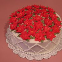 Poinsettia Cake Royal icing poinsettias on buttercream-covered cake.