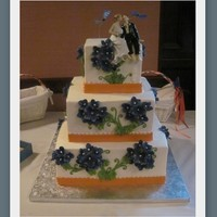 "Hydrangea Wedding Cake 12"" 9"" and 6"". BC with fondant orange ribbon. Hydrangea were GP. Leaves & vines were BC. What a pain - nothing would..."