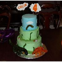 Dinosaur Birthday Cake 4th birthday cake for my son. IMBC with fondant accents and RKT dinosaurs covered in fondant and hand-painted. Inspired largely by jaklotz1...